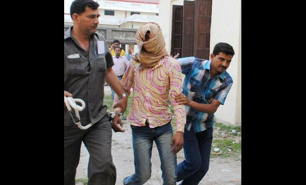 Delhi Police personnel take away Manoj Kumar, who has been accused of brutally raping a five-year-old girl in the capital, in Muzaffarpur in Bihar