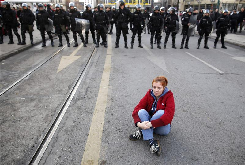 An anti-government protester sits on the ground in front of police during a demonstration in Sarajevo
