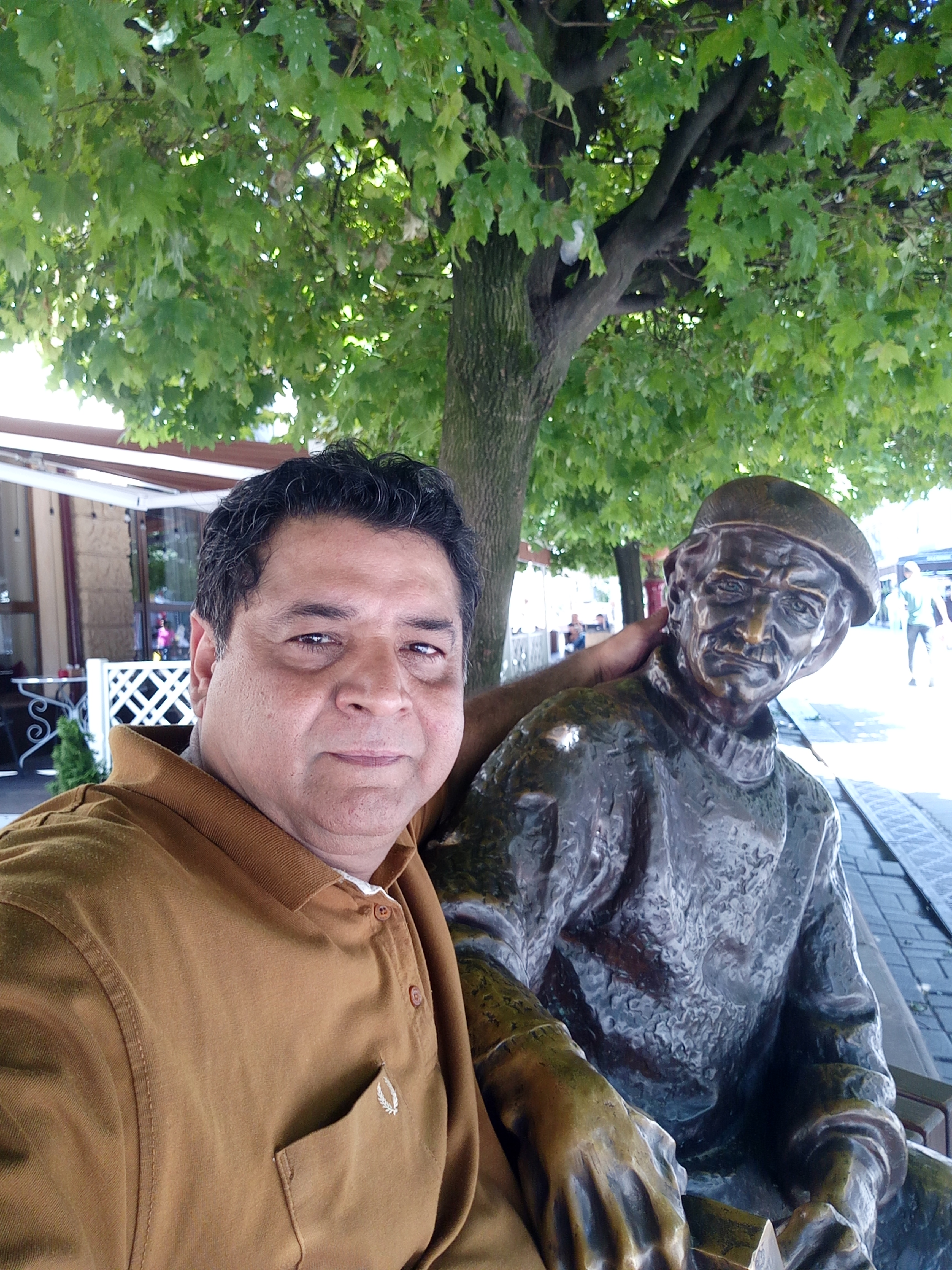 Ivano Frankivsk . In Square (Rynok---Bazaar), he tells me sitting under a tree in hot day of summer can offer you acquaintance to someone you do not know-- Travel for Cause ---