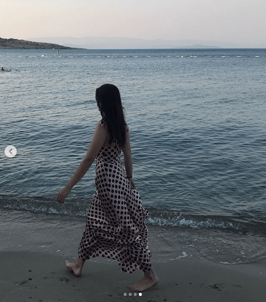 Esra is reading a book while lying on a boat and the other photo shows her walking on a beach.