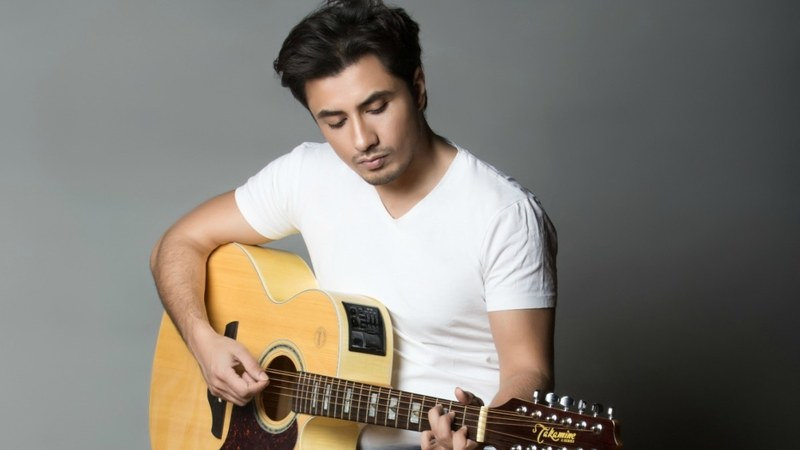 """All-time famous singer Ali Zafar has paid tribute to the legendary Junaid Jamshed by remembering him on his birthday. This exclusive wish has emotionally linked fans to the memory of Vital Signs and Junaid Jamshed. Ali Zafar made JJ's birthday wish special by singing 'Aitebaar'. It nostalgically connected fans to the evergreen songs produced by Vital Signs in the soulful voice of Junaid Jamshed. Ali Zafar Sings Aitebaar on JJ's Birthday! Junaid Jamshed would have been of 56 years as September 3rd is marked as his birthday. To make everyone feel his presence even today, Ali Zafar sang Junaid Jamshed's one of the most popular songs, 'Aitebaar'. Here is how Ali Zafar wished JJ on Twitter. He penned the birthday wish as, """"Happy 56th birthday dear Junaid Jamshed. You will always rule our hearts. Rest in peace. Sharing my little tribute again."""" Watch this video for Aitebaar's cover by Ali Zafar! About Junaid Jamshed Junaid Jamshed is the name that doesn't need any introduction. He has always been the one in the millions. He gained prominence and international recognition with his band named 'Vital Signs'. The first album was launched in 1987 from which Dil Dil Pakistan made Junaid Jamshed mount the peak of fame. Dil Dil Pakistan is called the second national anthem of Pakistan now. The commercial success of Vital Signs' first album helped develop Pakistan's rock music industry. In 2004, Junaid Jamshed took major decision of leaving music career and devoted himself to the path of religion, Islam. This period made him emerge as an Islamic scholar and preacher. Junaid Jamshed's Death Junaid Jamshed was on his mission to preach Islam in different regions of Pakistan. His second wife Nahya Junaid was also on this journey along with him. The couple died on 7th December 2016 when PIA Flight 661 crashed in Havelian. The flight was en route to Islamabad from Chitral. Junaid Jamshed's Children Junaid Jamshed has left behind three sons and a daughter. His sons stay active on social """