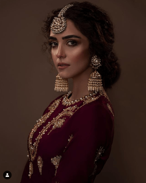 The magnificent Maya Ali has once again impressed her fans with a spellbinding photoshoot as she dresses up with a charm in bridal wear. She has invested her energy in the expressions to make this shoot worthwhile. The deep sensational maroon and that of a classy combination of green and red with a fine sprinkle of embellishment make everything highly captivating. Ali Xeeshan has always made sure to go out of the way and in doing so, this photoshoot is all that we can think of in terms of wedding fantasies. Check out this latest photoshoot of Maya Ali that will leave you speechless! Maya Ali Spellbinding in Maroon Bridal Wear Check out these clicks of a fascinating photoshoot of Maya Ali in which she has donned Xeeshan Ali's bridal wear. Her expressions and the way she has carried the dress is all that it takes for a charming photo session. Take a look! Maya Wears the Blend of Red & Green from Bridal Collection The combination of red and green is one of the lesser choices however, the way Xeeshan Ali has designed this bridal wear, is absolutely gorgeous. The stylish back and layered fusion of red and green that is all embellished exquisitely make it something perfect for this season. Check out Maya Ali wearing this beautiful bridal wear with a traditional touch! Maya's hairdo and makeover are looking awesome in relevance to this fancy dress as Shoaib Khan has worked with brilliance. Her bangles and the heavy necklace is a true depiction of a traditional bride. About Maya Ali Maryam Tanveer known by her stage name Maya Ali, is a Pakistani actress, model, and VJ. She is mostly known for her roles in Pakistani television serials and the film industry. Maya made her film debut with the 2018 action-drama film Teefa in Trouble opposite Ali Zafar. After this movie, she worked in a leading role in the romantic-comedy film Parey Hut Love in 2019 opposite Sheheryar Munawar. Both of these movies were commercially successful and the former earned her nomination for Best Actress