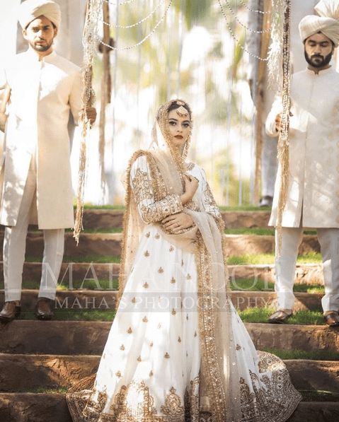 Minal Khan has been in the limelight these days for her different photoshoots. Although she received massive criticism for a recent shoot she got done with for a shoe brand, however, she is back with grace once again. Minal is wearing Maha Wajahat's bridal wear and looking heavenly stunning in all of these clicks. Here we have got Minal Khan's latest photoshoot! Minal Khan Dons White Bridal Wear for Latest Photoshoot! Minal and Aiman have been one step ahead always to impress their fans with something elegant. As Aiman is busy with her family life these days, so Minal is continuing to do wonders. In her latest photoshoot, she has dressed up in beautiful white bridal wear with golden embellishment making Minal stand out. Check out these clicks that will leave you stunned! The fine combination of elegance and tradition, this dress is enhanced with charming personality of Minal Khan. Take a look on more clicks! Minal has carried herself so appropriately while keeping the shyness of a traditional bride intact throughout. Her makeover with the deep red lipcolor has added up to the beauty of this luxurious design of the bridal wear. Unveiling the gorgeous bride with the merriment of new beginning on her face, this picture is all about perfection. The flower petals depict the colors and fragrances spreading around welcoming a big change in life. This dress has got a wide-spreading flare with artistic fancy work at the borders. The dupatta is made into net clothing and embellishment is sparkling all over it. Minal Khan has given her fans a reflection of her look as a bride that is out beyond the words of praise. Maha Wajahat also shared a picture in which she has asked for the opinion regarding which bride is looking more beautiful in white dress. One of these gorgeous brides is Minal Khan while other one is Hareem Farooq. Here we have got the picture for you all to decide it by yourself. In addition to this photoshoot, here we have got a short video clip of Minal Khan from