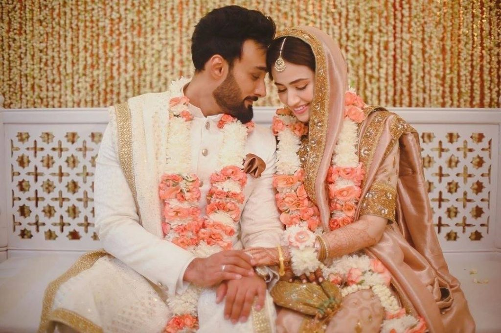"""The gorgeous princess of the industry Sana Javed and the rockstar Umair Jaswal have recently tied the knot. As soon as this news broke on social media, the fans couldn't resist being a part of this merriment. The couple looked absolutely stunning in the peachy hues and that got a reflection of their serene smiles stretched wide on their faces. This news is still making rounds over the internet with new pictures revealing from the event. Here we have got some of the unseen clicks from the wedding ceremony of Sana and Umair. Take a look! The Unseen Wedding Clicks of Sana Javed with Umair Jaswal! As we know that the news of the couple's nikkah surfaced with a single click posted by Umair Jaswal and with time, more pictures made their way to social media. Here we have got some of the unseen wedding clicks! And... here we have some pictures from Umair Jaswal's family including his brothers and parents. Check out some more clicks from Sana Javed's family including her siblings all dressed up elegantly. Take a look! The Post-Wedding Picture of Sana and Umair! Have you seen this post-wedding picture of Sana with Umair? If not, then here we have it for you. Check it out! Umair Jaswal Thanks Everyone for All The Love! Umair Jaswal took it to Instagram to express his love and gratitude for all those who have showered their love on the new beginning of their life. He posted the picture with the following caption: """"THANKYOU SO VERY MUCH FOR ALL THE WARMTH, LOVE, AND THE HEARTFELT BLESSINGS. 😊 WE ARE BLESSED TO HAVE SO MANY LOVED ONES AROUND US. MEANS THE WORLD TO US ❤ WE WISH WE COULD THANK EACH AND EVERY SINGLE ONE OF YOU INDIVIDUALLY. ❤ PLEASE REMEMBER US IN YOUR PRAYERS. LOTS OF LOVE THANKYOU AND GOD BLESS 😊 US"""" And... here we have Umair's exclusive Insta post! So, what do you think about this new couple in the town? Keep sharing your valuable feedback with us!"""