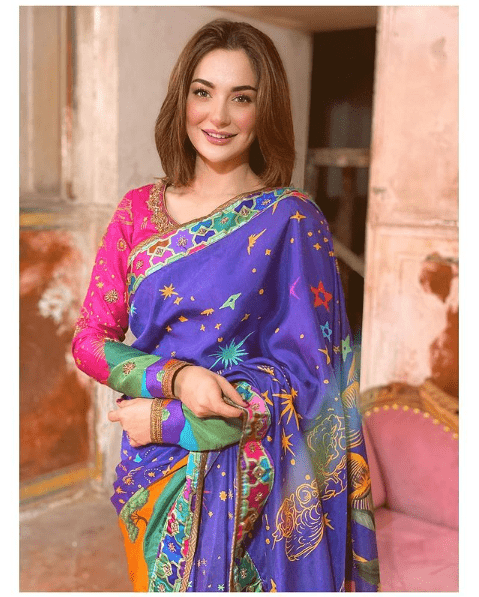 The ever-stunning Hania Amir has always mesmerized her fans with her gorgeous looks. She looks pretty in whatever she wears and that makes her special. From eastern to western, whatever Hania wears, she makes sure to leave her fans spellbound. Here we have got a collection of pictures in which Hania flaunts the grace with her luxuriously beautiful saree. Take a look! Hania Amir Flaunts Sensational Saree Look! Check out these mesmerizing pictures of Hania Amir wearing most beautifully designed sarees that will leave you stunned. Have a look! Hania Amir All Covered In Rainbow! This is the latest picture of Hania wearing a rainbow saree that is so elegant and vibrant to enhance her gorgeous looks. The stuff of this saree also looks luxurious and perfect to wear at semi-formal as well as formal occasions. Her no-makeup look is looking perfect with this colourful saree and Hania has definitely carried it with grace. The Floral Delicate Pink Saree! Hania Amir seems to be standing amid a garden of pink flowers spreading fragrance all around. This floral delicate saree is an epitome of grace and Hania has made sure to carry it with a class! Hania in Glitzy Maroon Saree! Looking for something exquisite to wear on wedding? Check out Hania' glitzy maroon saree that is making her look hot an stunning. The net clothing and embellishment settled all over the saree has made it a masterpiece. Simple Yet Elegant Red & Black Lining Saree! Go simple yet elegant with this beautiful red and black lining saree on semi-formal occasions. The silky look of the cloth has beautified this saree while making Hania look outclass! When White Is All About Grace! Hania Amir looks stunning in luxurious white saree. The borders are finely studded with fancy embellishment hile the delicate see-through fabric gives this saree a classy look. Hania Slaying in Mauve Saree! Mauve colour is rarely available specifically when it comes to clothing collection. Saree looks so stylish on Hania in fancy mauve. Ta