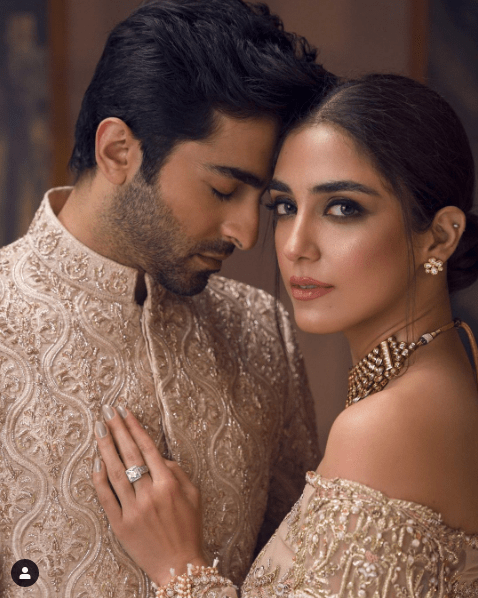 The ever-gorgeous Maya Ali and hearththrob Sheheryar Munawar have come together to impress their fans with something outclass. Although they are both brilliant actors and have shown their talent in different drama serials, however, this photoshoot is an entirely different story. The way they have shared chemistry as a couple and the feel of this shoot is quick to indulge you in its charm. Well... no more what! Here we have got this hot photoshoot of Maya and Sheheryar that will definitely blow you away! Maya Ali and Sheheryar Munawar's Latest Hot Shoot! Sheheryar Munawar is already turning on the heat with her different photoshoots going viral on social media. His recent shoot with the pretiest actress Syra Yousuf had been in the limelight for the wonderful chemistry and the bold feel. Now Sheheryar has joined Maya Ali in this latest photoshoot which is a story of romance that a stunning couple shares in wedding attires. Take a look at these hot clicks! Maya Ali goes with a nude peach canvas that is deftly adorned with detailed florals, handworked chandeliers and tendrils. This luxurious attire is perfectly tailored to gracefully hug the curves while this silhouette is layered with a long net veil featuring embellishments and embroideries on the border. The class of the art and design in the most charming attire is hypnotizing Sheheryar with Maya's charm in this luxuriously crafted piece. It is glam encrusted, curve hugging bridal silhouette, that instantly gains attention. The prince coat is artfully embellished with motifs derived from Mughal jaali work. This flattering fit is tailored to accentuate the body shape, showcasing the exquisite craftsmanship of our artisans. Maya and Sheheryar - What's In The Gossips? Well... Maya Ali and Sheheryar Munawar these days are known as a rumored couple these days. However, there is no official statement from either of the celebrities in this regard. Previously, Maya had a lovely relation with Osman Khalid Butt, however, all 