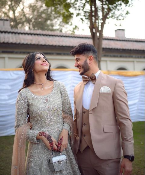"""The famous Canadian-Pakistani YouTuber Shahveer Jafry has finally got engaged with Ayesha Baig. Shahveer surprised his fans with his post on Twitter having adorable clicks from the his engagement ceremony. He penned down the caption with the post as: """"WE ARE ENGAGED!"""" Here we have got further details and mesmerizing event pictures in which the couple is looking absolutely stunning. Shahveer Jafry and Ayesha Baig's Engagement Pictures! Here we have got the pictures from this beautiful ceremony that made Shahveer and Ayesha exchange their engagement rings. Take a look at these clicks! Shaveer is looking deboniar in this perfect to wear suit and the colour is so different that is making him stand out. Moreover, the colour of Shahveer's dress is going with the theme of Ayesha's bridal wear. She is looking absolutely gorgeous! The shyness on the face of Shahveer's fiancee is worthy to observe as it is enhancing her charming look in a unique manner. The glow of her eyes is depicting her pleasure in beginning her life with Shahveer Jafry. The finest yet creative embellishment with a combination of exquisite embroidery looks like the designer has invested good time and energy on this wear. Shahveer's dress in combination to that of Ayesha Baig is already making them look 'made for each other' sort of a couple. Here comes Shahveer's friend Sham Idrees who was there to make this day special for his friend. The lovely cake cutting ceremony is adding up to the glam of this beautiful event marking the togetherness of two love birds. Look! Who is here! Yes, Noor Zafar Khan also attended Shahveer's engagement and she is looking elegant yet super-stunning! No picture can be as much beautiful as this one because the beautiful Mom has accompanied Shahveer in the click! Shahveer has always entertained us with her amazing videos on YouTube while hitting jokes even through the most normal situations. He is such a talented guy who has constantly gathered praise until the date. That's the"""