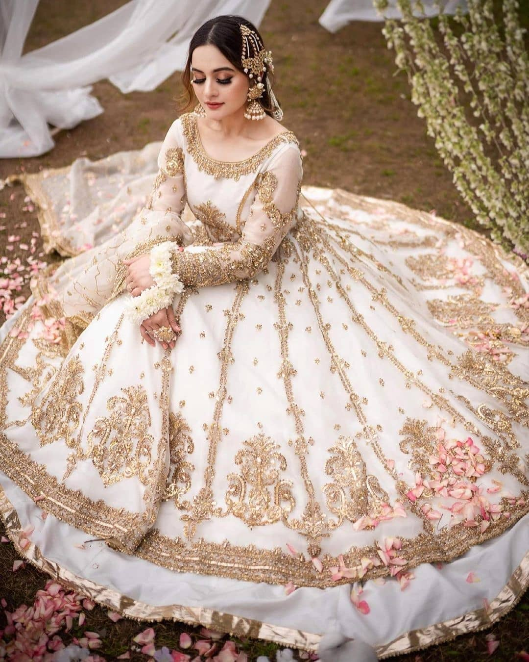 Well… it's been so long to see Aiman Khan showing up for any of the projects coming her way specifically after her marriage and birth of Amal. However, she has finally made a comeback with a mesmerizing photoshoot that will leave you enchanted. She flaunts the grace with such a perfection that makes one fail to keep eyes away from her clicks. We know that Aiman is an absolutely fantastic actress and she knows the way to gain the attention of her fans as well. This time, her photoshoot has turned on the game. Check out these clicks and make your day!  Aiman Khan Looks Drop-Dead Gorgeous in Her Latest Photoshoot!  It is not up to the words only, Aiman is actually looking drop-dead gorgeous in her latest photoshoot. She has donned a luxurious fancy bridal outfit that makes her sway in elegance. The way she is feeling comfortable in wearing it makes us have an idea that it is a perfect wear for new brides this season. Her makeover is the finest combination with the dress as it highlights her features in an alluring manner.  On the other hand, Aiman's hairdo is somewhat that from a fairytale make it a whole new love story to reveal for everyone. Her jewellery is royal yet classy that makes her stand out as a bride. Now check out these mesmerizing clicks of Aiman Khan that will leave you stunned!           The finest embellished embroidery all over the white base of this bridal outfit is a creative blend of tradition and the latest fashion trends. Moreover, Aiman's jhumkas are linking directly to the fancy work on the dress which is making it something outclass.  So, what do you think about this fantastic comeback of Aiman Khan with this classy photoshoot? Don't forget to share your valuable feedback with us!